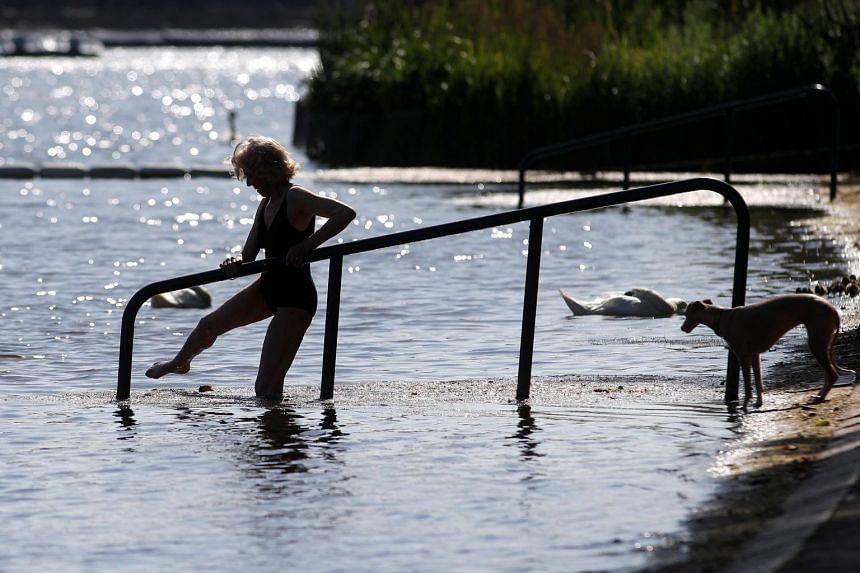 A woman enters the Serpentine lake in Hyde Park, London, as warm weather arrives across Britain, on June 27, 2019.