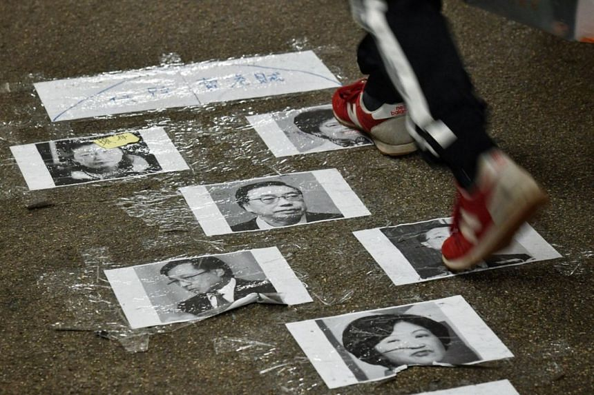 """At more than one Lennon Wall, protesters taped pictures of Hong Kong leader Carrie Lam and pro-Beijing lawmakers to the floor to create """"democracy dance pads"""" - and invited people to stomp on the images to music."""
