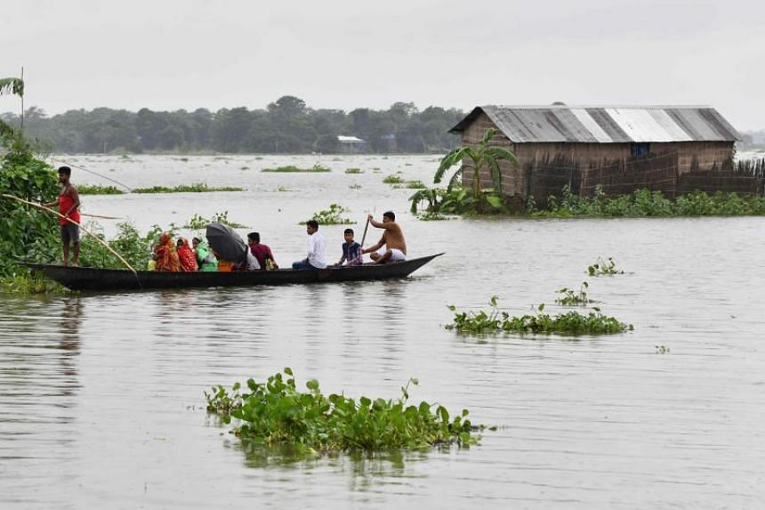 Indian villagers travel by boat through floodwaters near a partially submerged house in Balimukh village of Morigoan district in India's northeastern state of Assam on July 11, 2019.