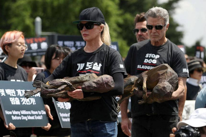 Basinger and Chris DeRose, president of Last Chance for Animals, hold mock dog meat during the rally.