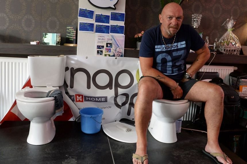 Belgian Jimmy de Frenne sits on a toilet in a cafe in an attempt to enter the Guinness Book of Records.