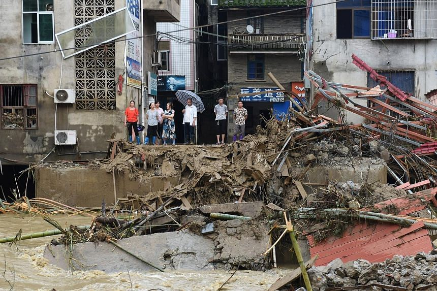 Residents on a river bank looking at the rubble of a bridge damaged by floods following heavy rainfall in Nanjing, China, on Tuesday. PHOTO: REUTERS