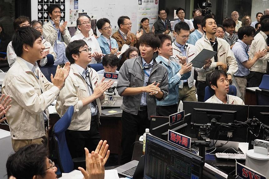 The Hayabusa2 probe landing on Ryugu. The findings of its mission may help shed light on the evolution of the solar system. Staff of the Japan Aerospace Exploration Agency celebrating after receiving confirmation of Hayabusa2's successful touchdown o