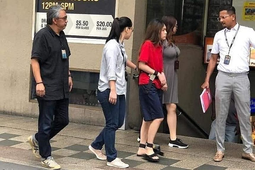 Murder accused Natalie Siow Yu Zhen (in red) being taken back to the crime scene at Orchard Towers. She is among the four still accused of murdering Mr Satheesh Noel Gobidass, who died following a brawl. LIANHE ZAO BAO FILE PHOTO