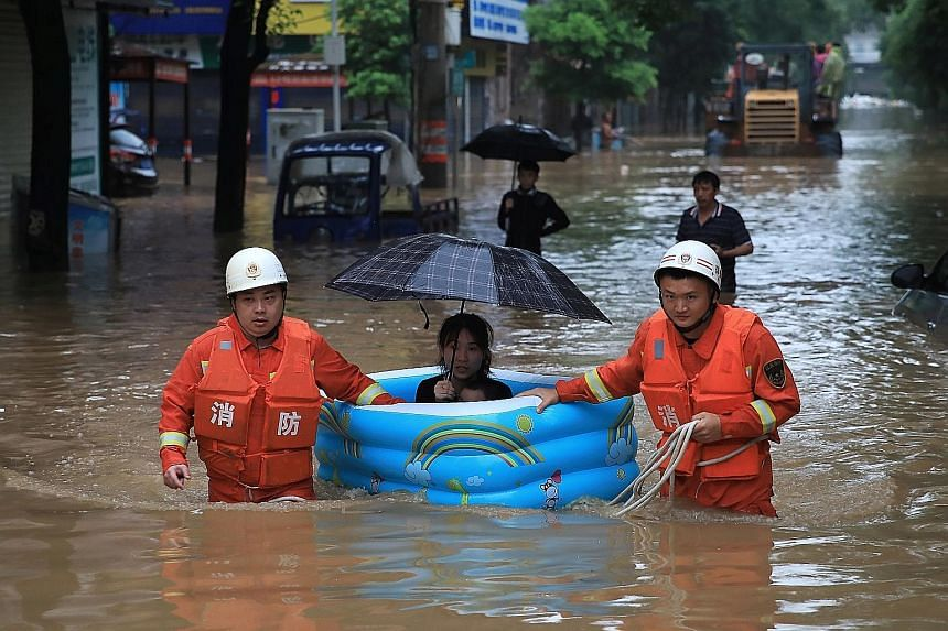 Rescue workers evacuating a woman following heavy rainfall in Pingxiang, Jiangxi province. The authorities in Jiangxi have triggered emergency responses and designated 17 million yuan (S$3.4 million) for flood prevention and rescue work. PHOTO: REUTE