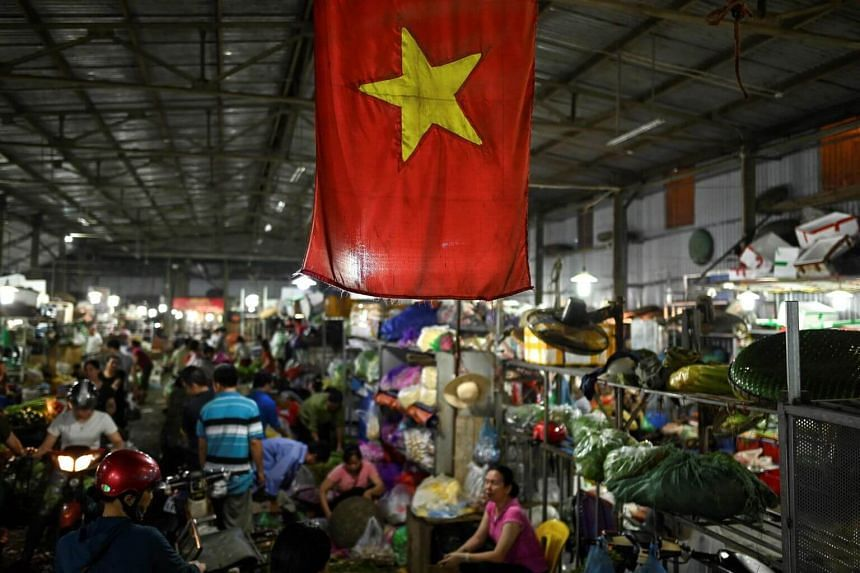 The Vietnamese flag is seen as vegetable vendors wait for customers at a wholesale market in Hanoi at dawn, on June 7, 2019.