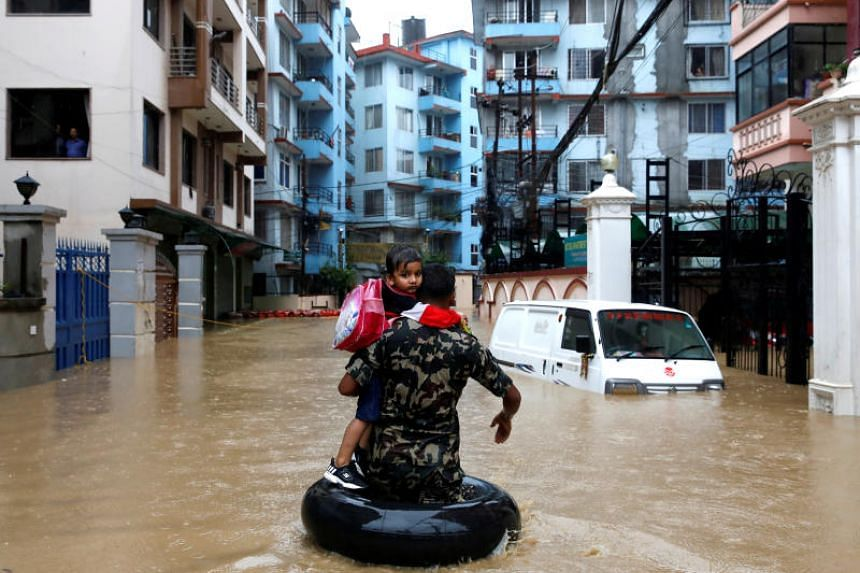 A member of the Nepalese army carrying a child walks along the flooded colony in Kathmandu, Nepal, on July 12, 2019.