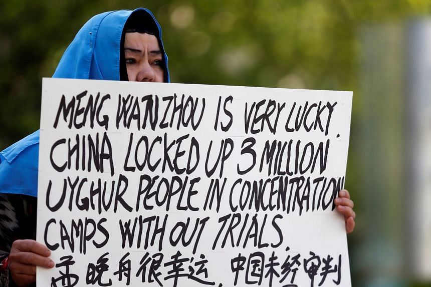 A woman protests China's treatment of Uighur people in the Xinjiang region during a court appearance by Huawei's financial chief Meng Wanzhou in Vancouver in May 2019.