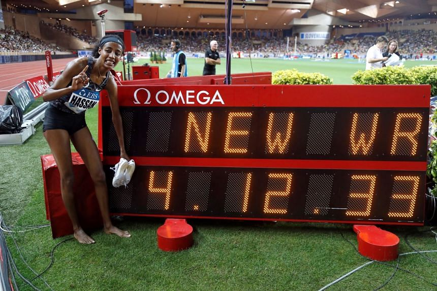 Hassan poses in front of a screen featuring her new world record time.