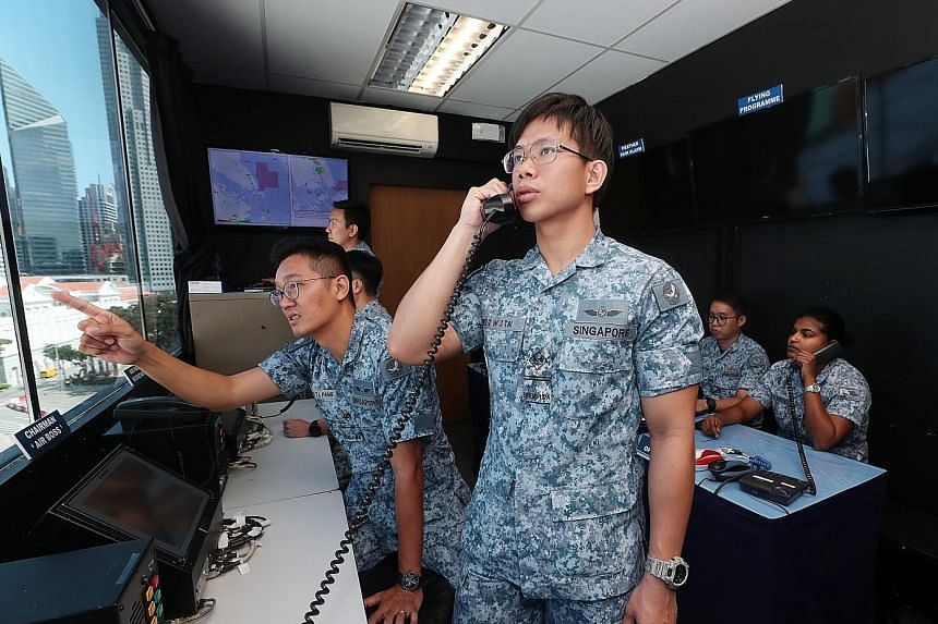 Military Expert 2 Tai Wei Jing (standing) and ME2 Pang Teck Lim (beside him), who are responsible for communications for the Air Participation Committee, at the control room at the National Gallery Singapore yesterday.