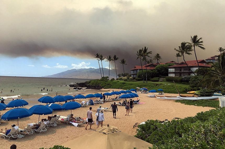 Smoke blanketing the sky as a wildfire spreads in Maui, Hawaii, on Thursday. Thousands were ordered to evacuate the area, while Kahului Airport was briefly closed and flights were diverted because of the smoke, which also forced the closure of two ma