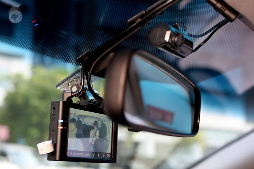 An in-vehicle recording device showing a driver and his passenger.