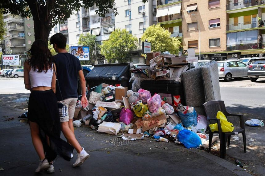 Residents walking past overflowing trash bins, on July 10, 2019, in Rome, as the Italian capital struggles with a renewed garbage emergency aggravated by the summer heat.