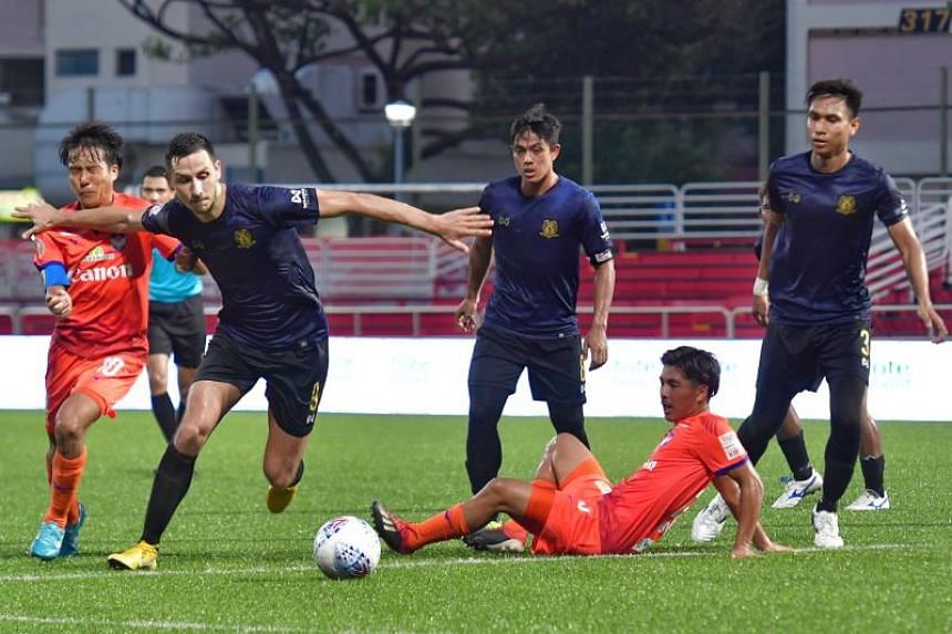 Hougang United forward #9 Stipe Plazibat (second from left) squares off with Albirex Niigata captain #10 Kyoga Nakamura (left) during the Singapore Premier League at Jurong East Stadium on July 13, 2019.