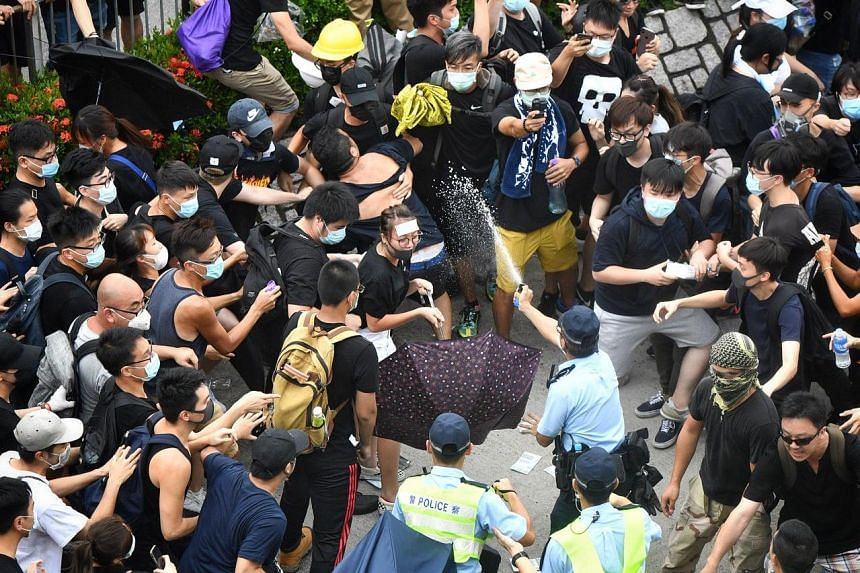 Protesters shield themselves as a policeman uses pepper spray on July 13, 2019.