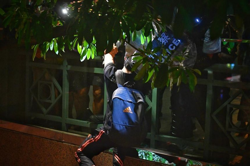 A protester hangs on for his life as bystanders and policemen pull him back up to an overhead bridge. The protester jumped over the barrier of an overhead bridge after being frightened by a police officer charging towards him with a baton.