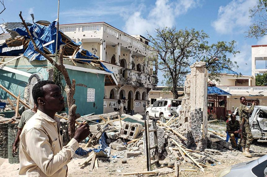 A man passes in front of the rubble of the popular Medina hotel of Kismayo on July 13, 2019.