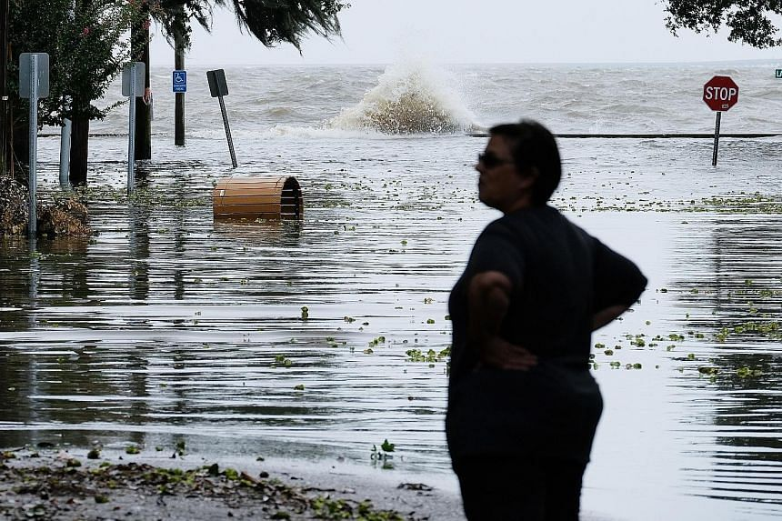 A woman in front of a flooded road near Lake Pontchartrain as Hurricane Barry approaches in Mandeville, Louisiana, yesterday. Mandatory evacuations have been ordered in outlying coastal areas beyond the protection of levees in Plaquemines and Jeffers