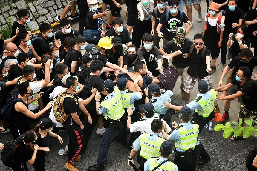 Hong Kong police clashing with black-clad protesters, who marched in Sheung Shui in the New Territories, not far from the Chinese city of Shenzhen, to voice their unhappiness over parallel importers yesterday. Critics say activities by the importers
