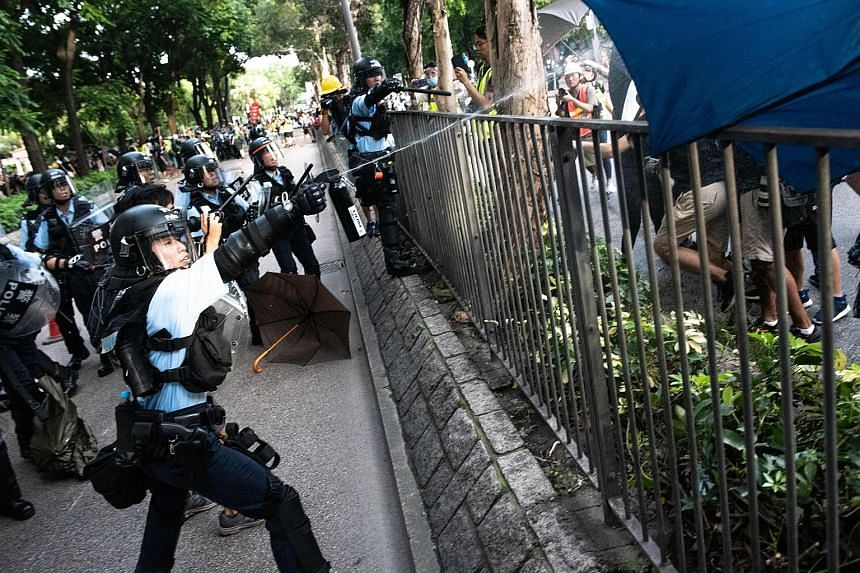 Left: A protester hanging on for his life as bystanders managed to hold on to him before policemen pulled him to safety. He had jumped over the barrier, not realising that he was on an overhead bridge. ST PHOTO: CHONG JUN LIANG