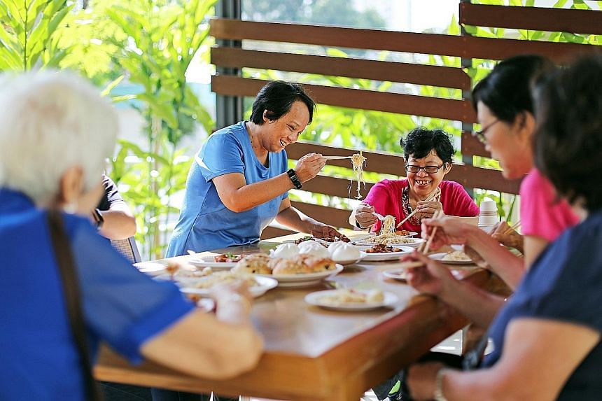 Having overcome her loneliness, Ms Jessie Teo (standing) is now befriending seniors in her neighbourhood through makan sessions, as well as helping those with dementia.