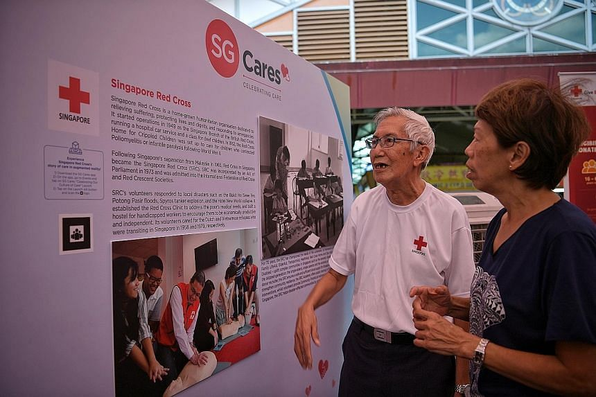 Singapore Red Cross volunteers Wan Fook Kum, 78, and Doris Yeoh, 62, at the third part of the SG Cares mural project at Chong Pang Amphitheatre yesterday. Mr Wan helped out during the Hotel New World collapse.