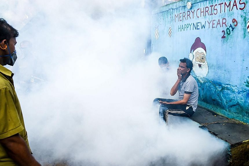 Mumbai residents being engulfed in smoke as municipal employees intensified preventive measures such as anti-malaria fumigation and fogging at a slum in the Indian city yesterday. The authorities have identified areas of the city with mills, railway