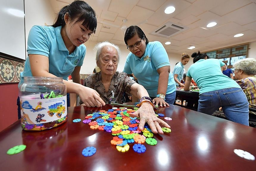 Madam How Lin Chi playing a game with guidance from her live-in caregiver Lai Lai Win (far left) and Ms Massuriyantee Othman (left), a healthcare assistant at Ghim Moh Senior Care Centre.