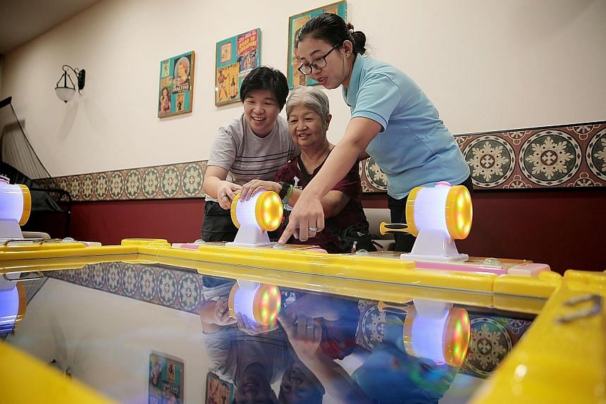 Madam Yong Lee Yoong taking part in a game with her daughter Sally Huang (left) and healthcare assistant Aye Thant Zin at Telok Blangah Senior Care Centre.