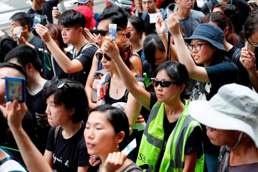 Journalists hold up their press cards as they stage a silent march to the Police Headquarters to denounce media treatment during a protest against an anti-extradition Bill, in Hong Kong, on July 14, 2019.