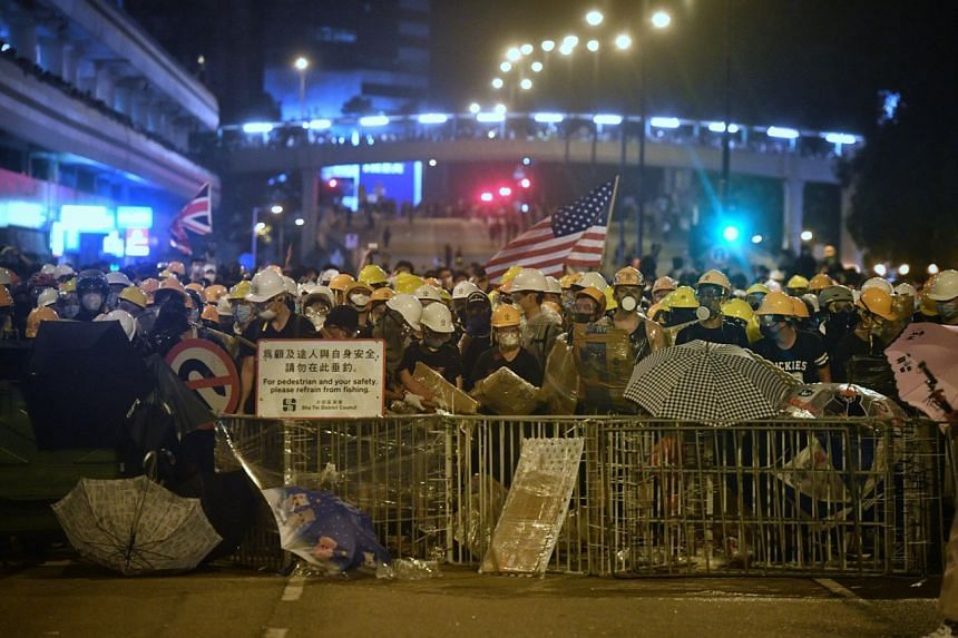 Protesters forming a human wall behind a barricade as they face off with Hong Kong police, during a demonstration on July 14, 2019.