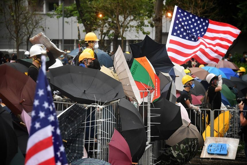 Protesters deploying umbrellas at a barricade as they face off with police officers, during a demonstration in Hong Kong on July 14, 2019.