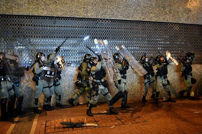 Hong Kong police officers taking cover under their shields as people throw things down at them, on July 14, 2019.