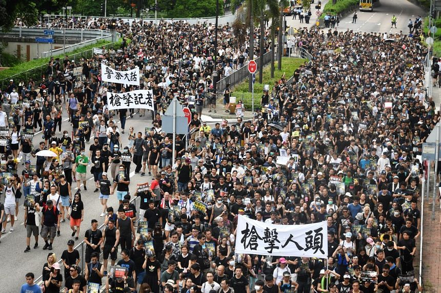 Protesters waving placards as they join a demonstration against a contentious anti-extradition Bill, in Sha Tin, Hong Kong, on July 14, 2019.