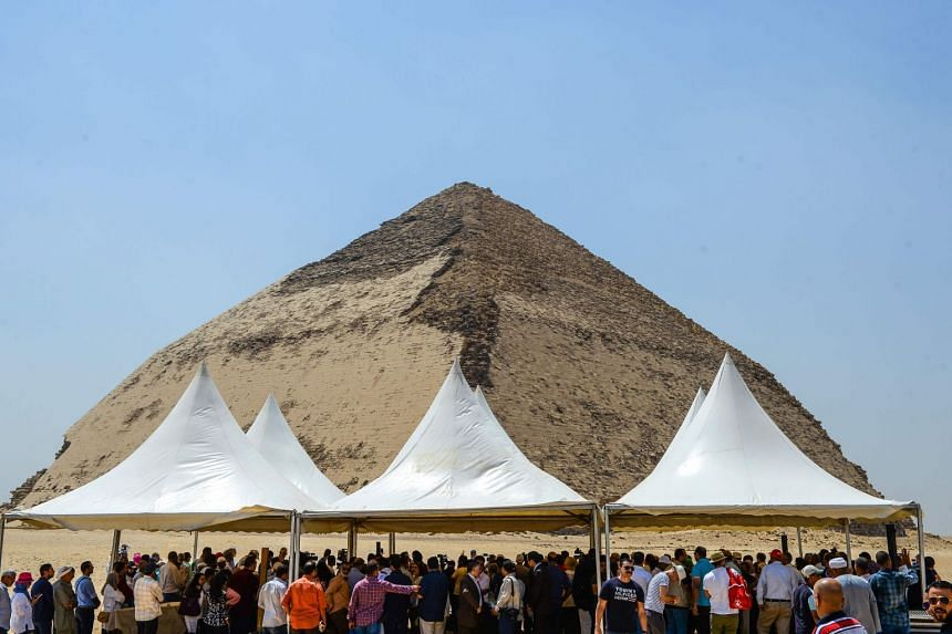People gather during an inaugural ceremony in front of the Bent pyramid of King Sneferu.