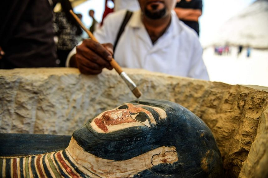 A man brushes dust from a newly-discovered sarcophagus.