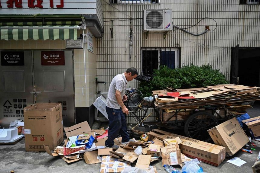 A man selects cardboard boxes from a waste deposit at a housing complex in the former French concession in Shanghai on July 11, 2019.