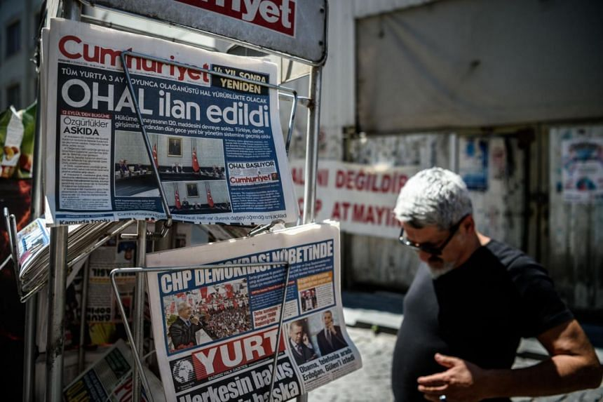 """A man reads newspapers front pages reading """"3 months state of emergency"""" near a shop in Istanbul, following the failed military coup attempt of July 15, in this file photo taken on July 21, 2016."""