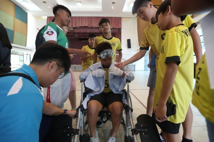 """Footballers helping a teammate wear clothes that simulate the challenges the elderly face, as part of an """"empathy workshop"""" on July 14, 2019."""