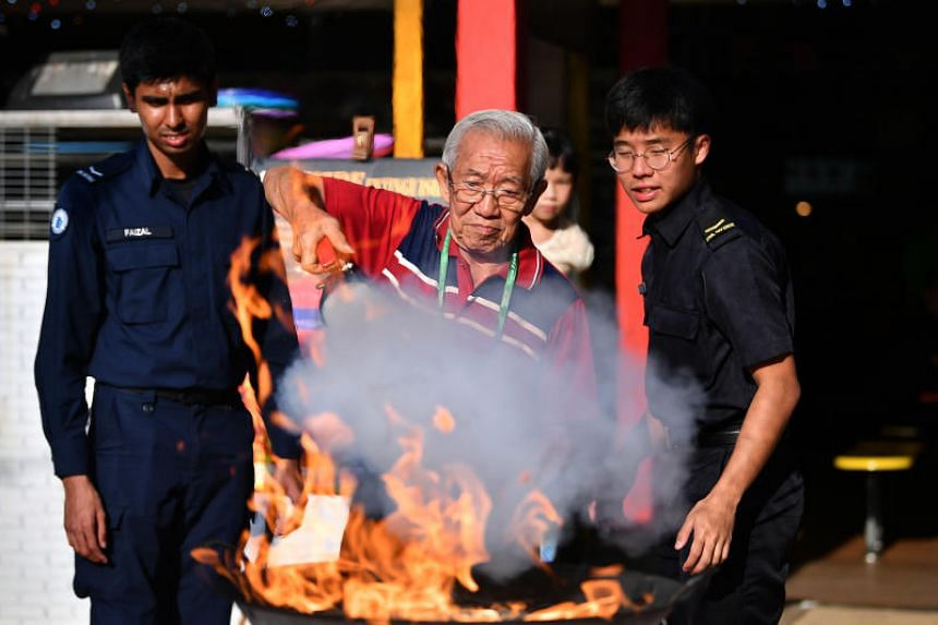 Retiree Tan Boon Tien learning how to use a fire extinguisher at West Coast Market Square on July 14, 2019.