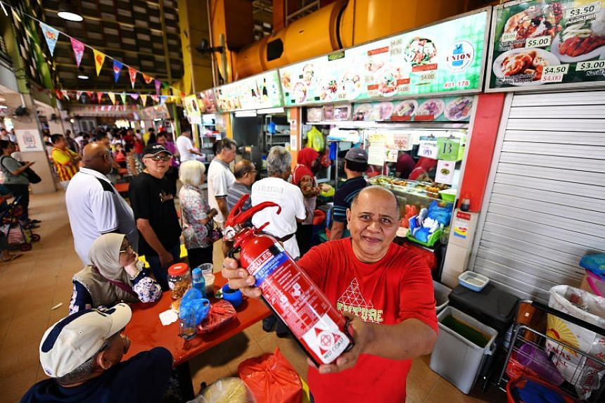 Mohd Zairuddin Bin Onan, owner of Hani Food Stall, holding a fire extinguisher at West Coast Market Square on July 14, 2019.