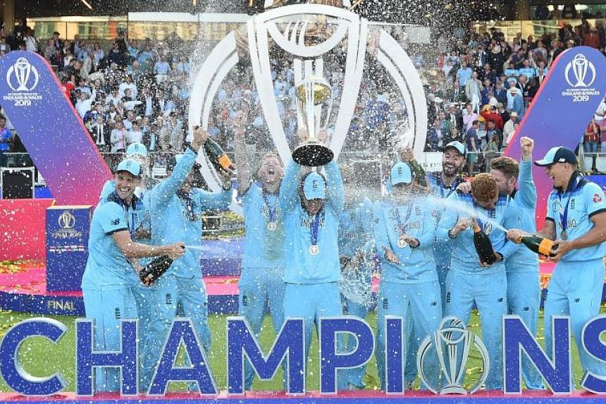 England's captain Eoin Morgan is sprayed with champagne as he lifts the World Cup trophy as England's players celebrate their win after the 2019 Cricket World Cup final between England and New Zealand at Lord's Cricket Ground in London, on July 14, 2