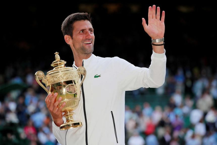 Serbia's Novak Djokovic poses with the trophy as he celebrates winning the final against Switzerland's Roger Federer.