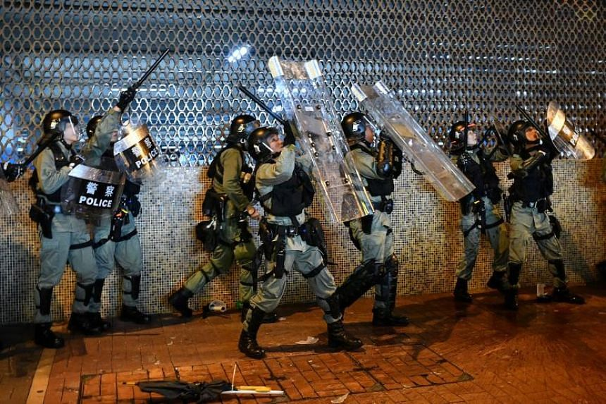 Police shield themselves from debris thrown from above at a protest in Hong Kong's Sha Tin area on July 14, 2019.
