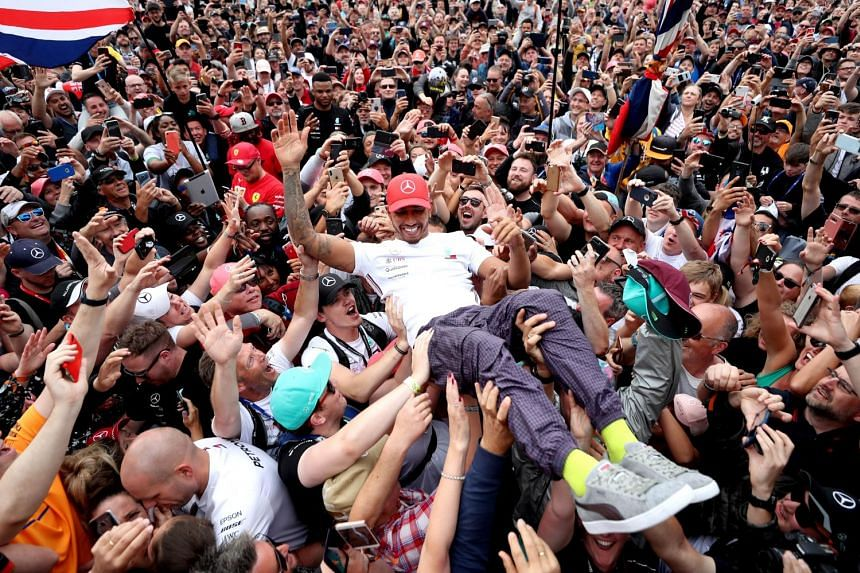 Mercedes' British Formula One driver Lewis Hamilton celebrating with fans after winning the British Grand Prix at Silverstone Circuit on July 14, 2019.