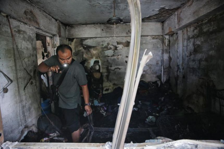 Mr Che Rohisyam Che Zain searches for belongings inside his flat where the fire originated, on July 16, 2019.