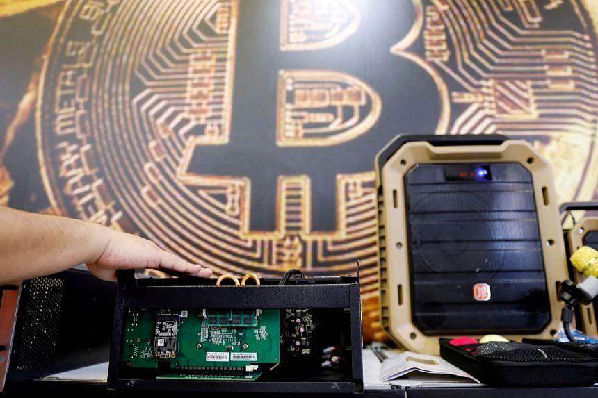A cryptocurrency mining computer is seen in front of bitcoin logo during the annual Computex computer exhibition in Taipei, Taiwan.