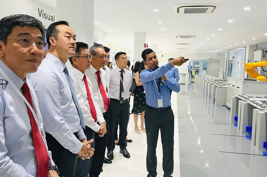 Senior Minister of State for Trade and Industry Koh Poh Koon (second from left) and Mr Jeremy Fong, chief executive of Fong's Engineering and Manufacturing (third from left), viewing Fong's new smart production line yesterday. The revamp is expected