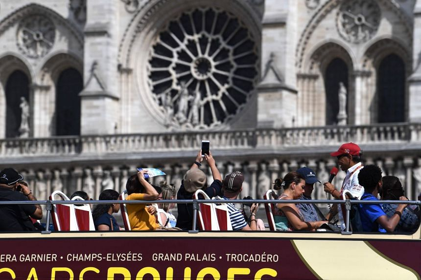 A tourist bus passes in front of Notre-Dame on July 13, 2019, in Paris.