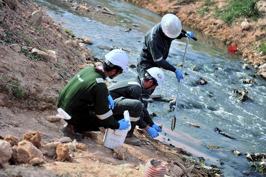 Officials taking samples of land to check air, water and soil levels at Sungai Kim Kim river, on March 19, 2019.